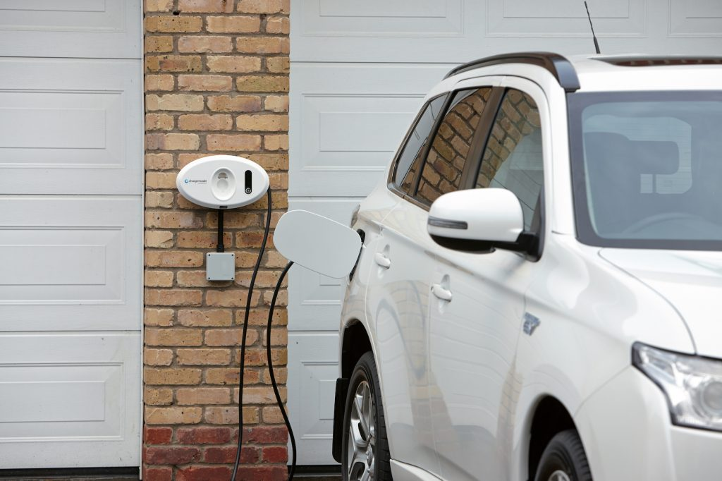 Chargemaster tethered white homecharge unit on garage charging Mitsubishi SUV