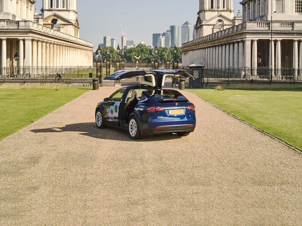 Tesla X type vehicle in the Greenwich area of London overlooking the city financial district