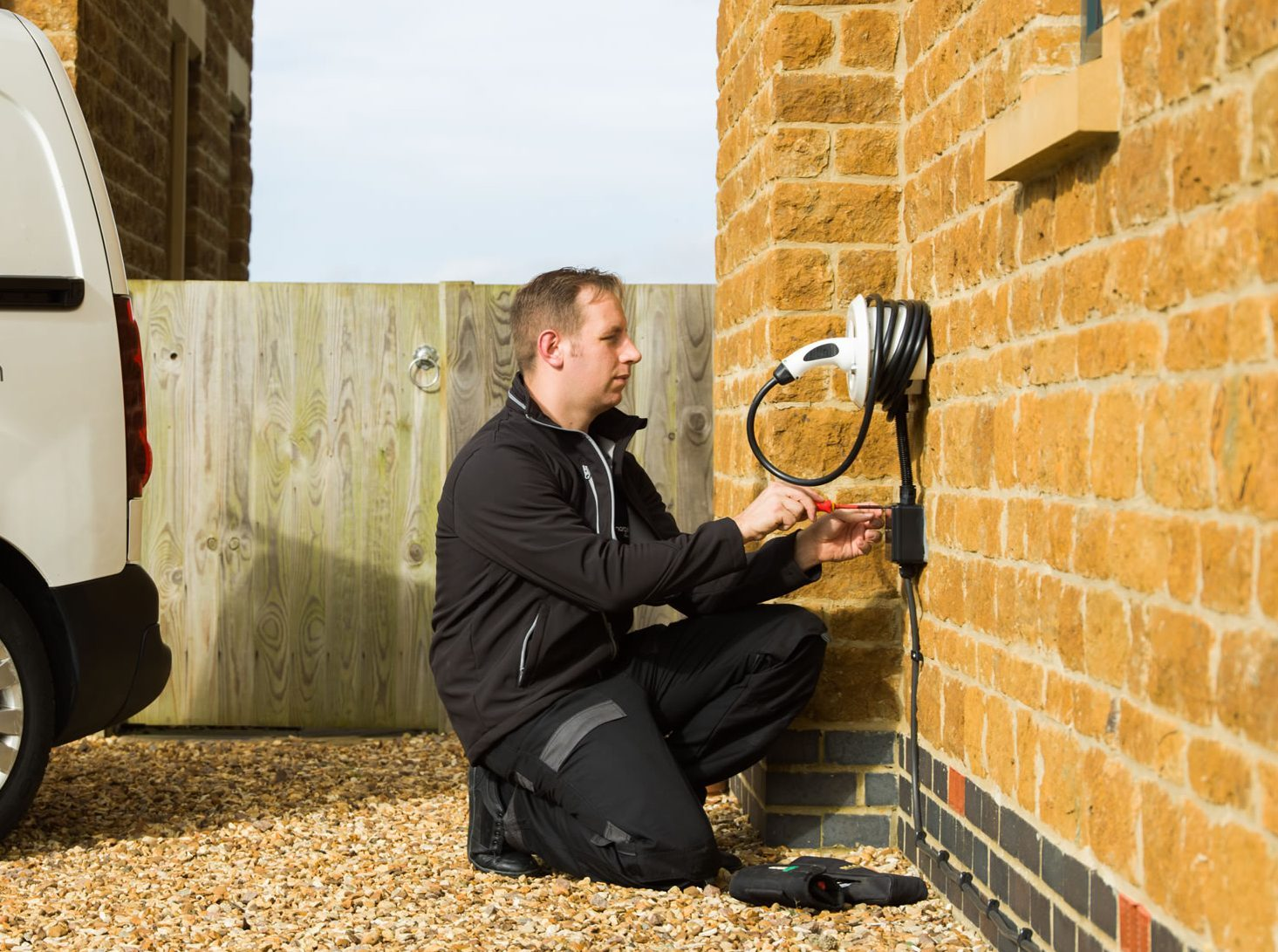 Engineer installing wall mounted white chargemaster homecharge unit